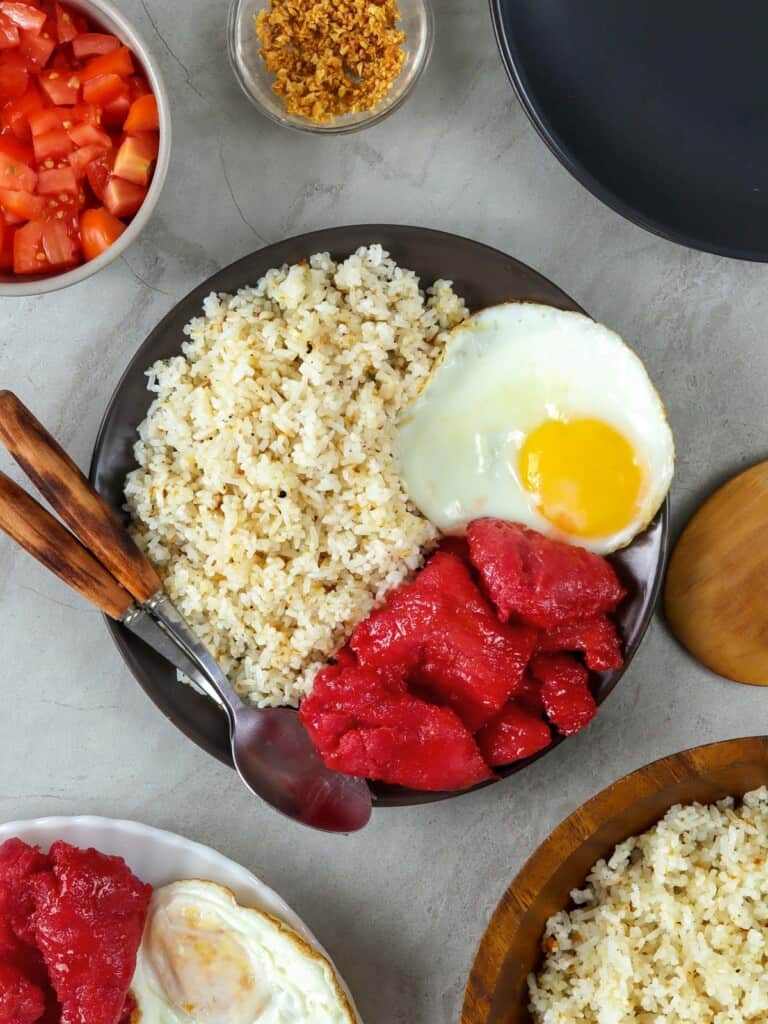 Filipino garlic rice on a black plate with tocino and fried egg