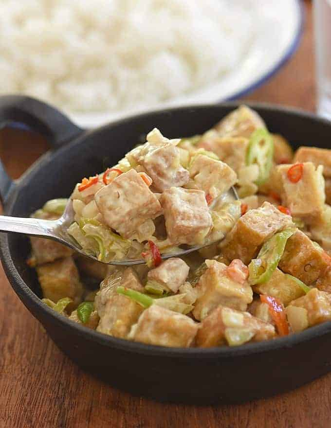 serving Sizzling Tofu Sisig with a spoon from a cast-iron skillet