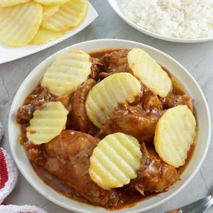 chicken asado with pan-fried potatoes in a white serving bowl with a plate of steamed rice on the side