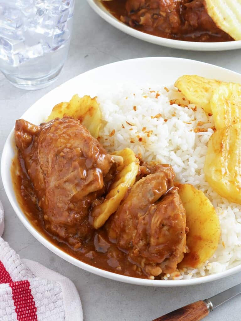 asadong manok with steamed rice on a white plate