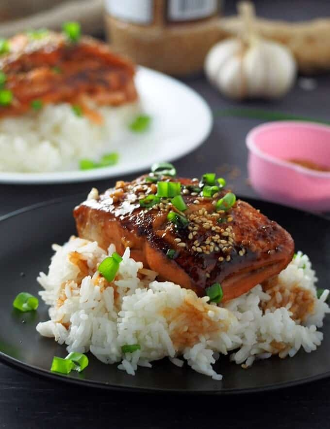 Teriyaki Salmon over steamed rice on a black plate