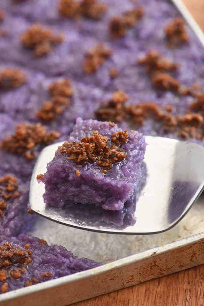 serving a slice of ube biko with latik topping from a aluminum pan