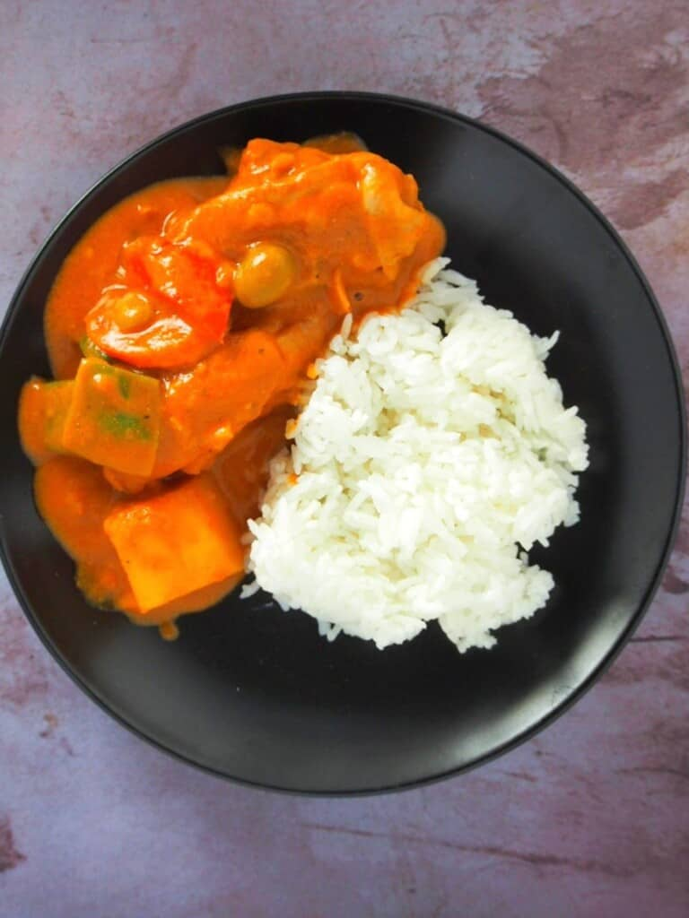 chicken caldereta with steamed rice on a black plate