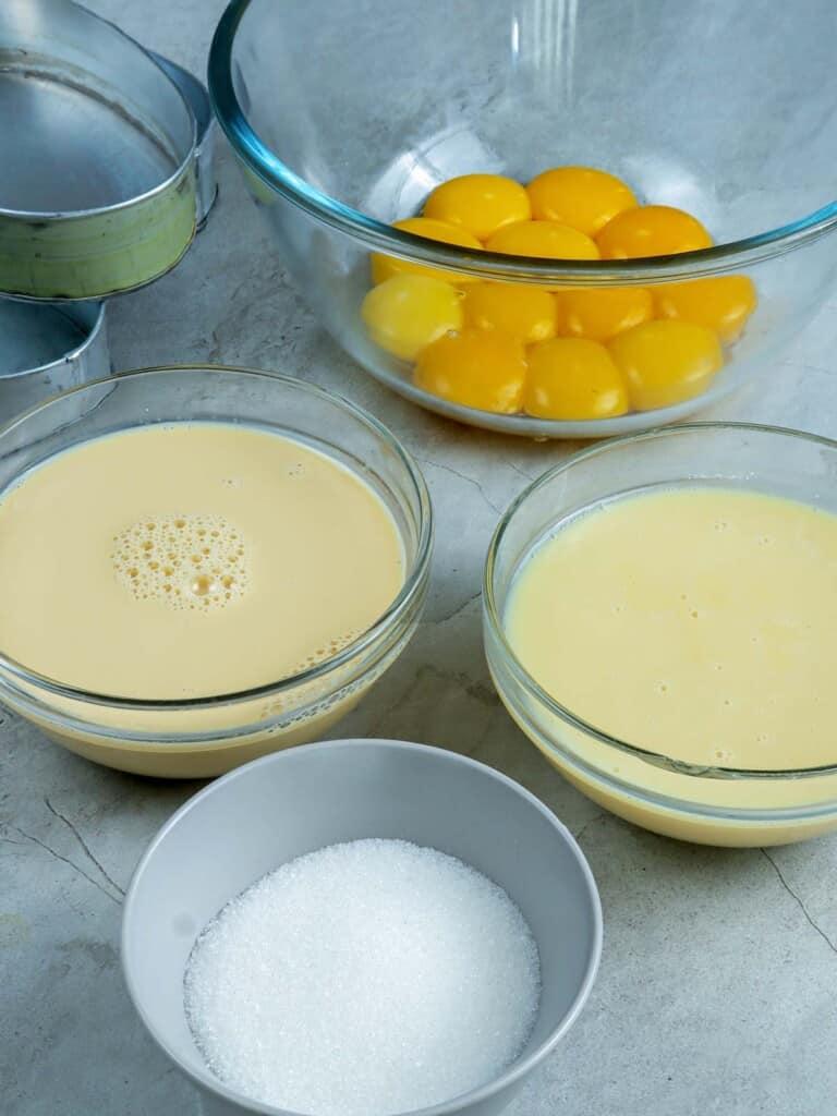 egg yolks, sugar, evaporated milk, condensed milk in bowls