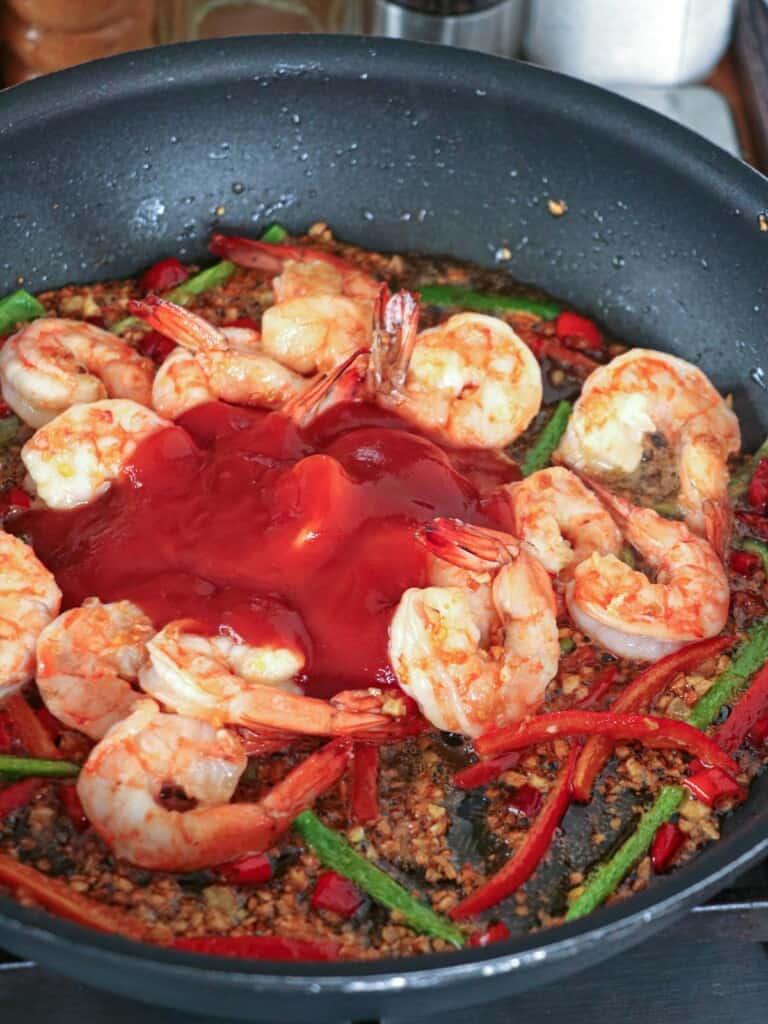 cooking shrimp in garlic in a wide pan