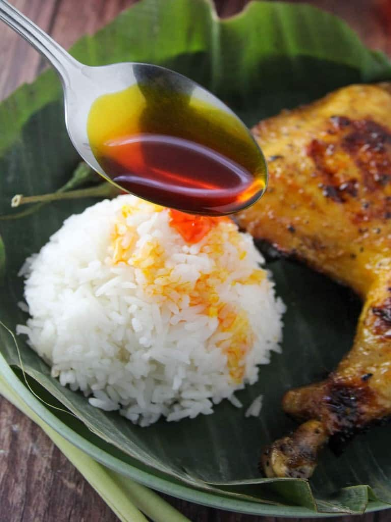 pouring chicken oil over rice
