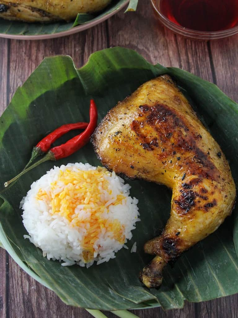 inasal na manok on a banana-lined plate with steamed rice and chili peppers