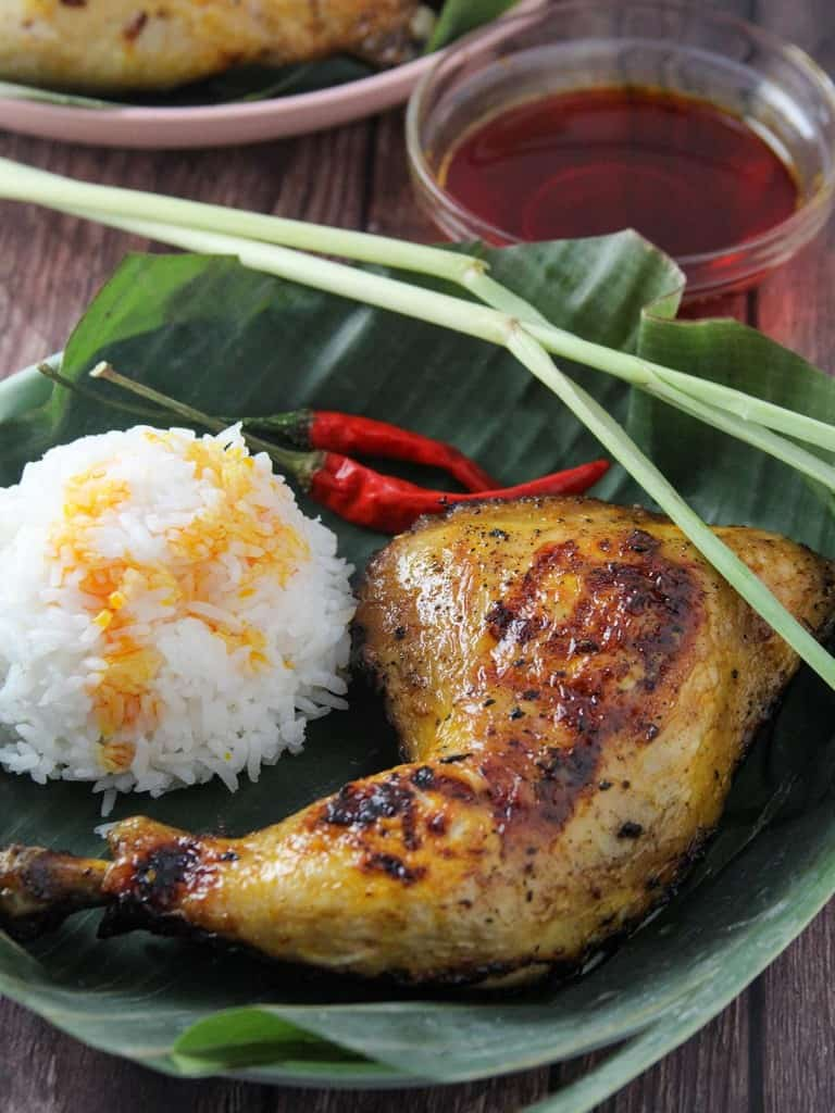 chicken inasal with steamed rice and chicken oil on a banana leaf-lined wooden plate