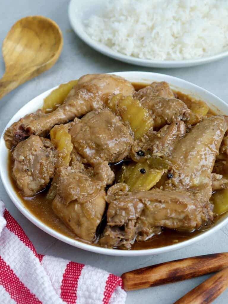 Chicken Adobo with potatoes in a serving bowl with a plate of steamed rice on the side