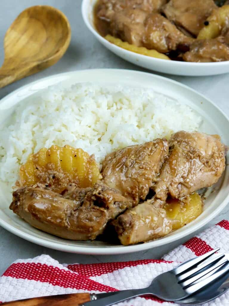 adobong manok with steamed rice on a white plate