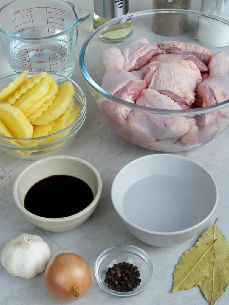 cut-up chicken, sliced potatoes, vinegar, soy sauce, water, onion, bay leaves, garlic, peppercorns in bowls