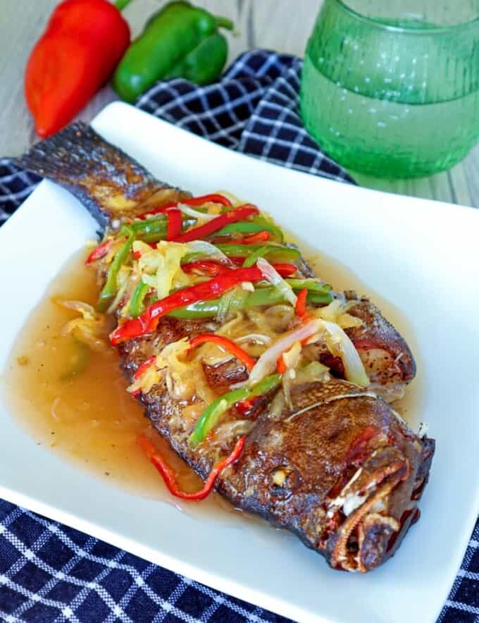 Escabeche Lapu Lapu topped with pickled bell peppers and shredded papaya on a serving platter