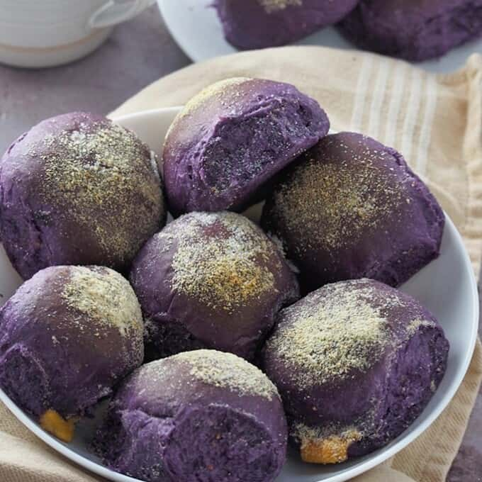 ube cheese pandesal on a white plate