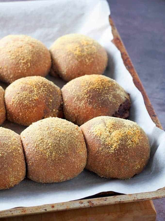 Chocolate Pandesal baked on a parchment-lined baking sheet