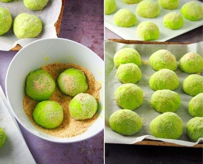 rolling pandan pandesal with ube halaya filling in breadcrumbs and placing on a parchment-lined baking sheet
