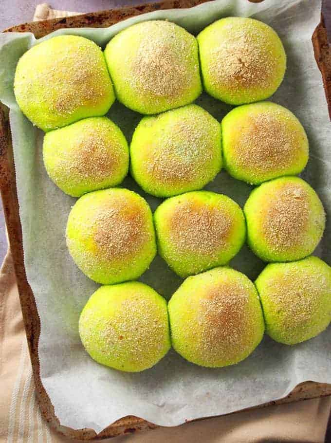 baked pandesal with pandan flavor on a parchment-lined baking sheet