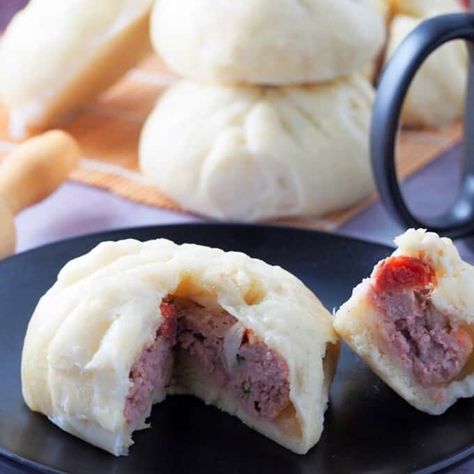 sliced siopao with meatball filling on a plate
