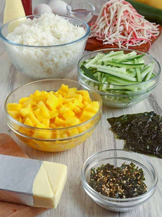 sushi rice, chopped mangoes, sliced cucumbers, nori sheets, furikake, imitation crab, cheese
