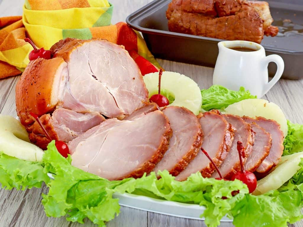 sliced Homemade Ham on a platter decorated with lettuce, pineapple rings, and maraschino cherries