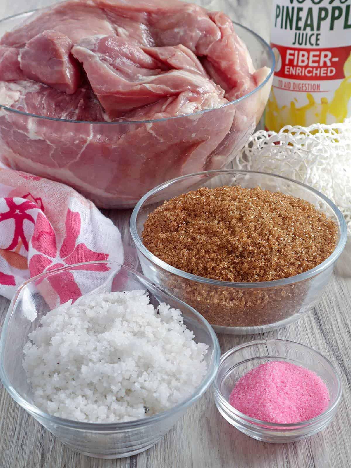 pork ham, brown sugar, rock salt, Prague salt in bowls and a can of Pineapple juice on the side