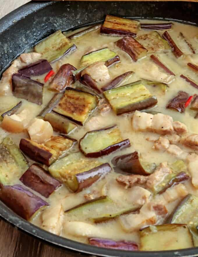 eggplant and pork in coconut sauce in a skillet