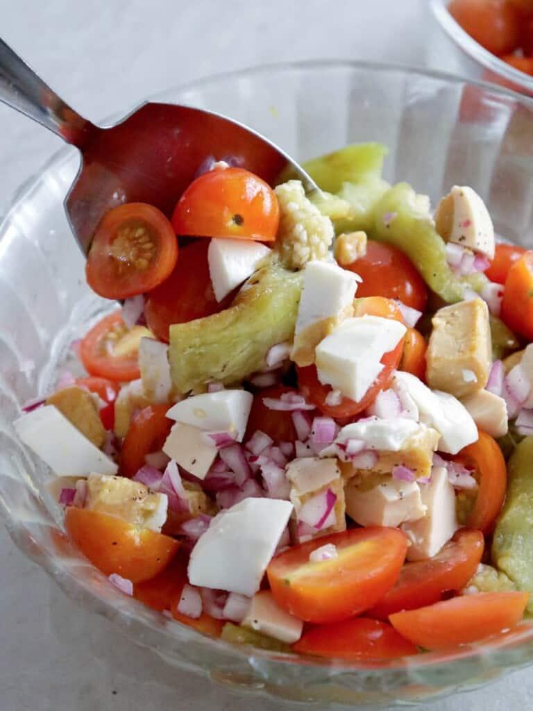 mixing ensaladang talong in a bowl