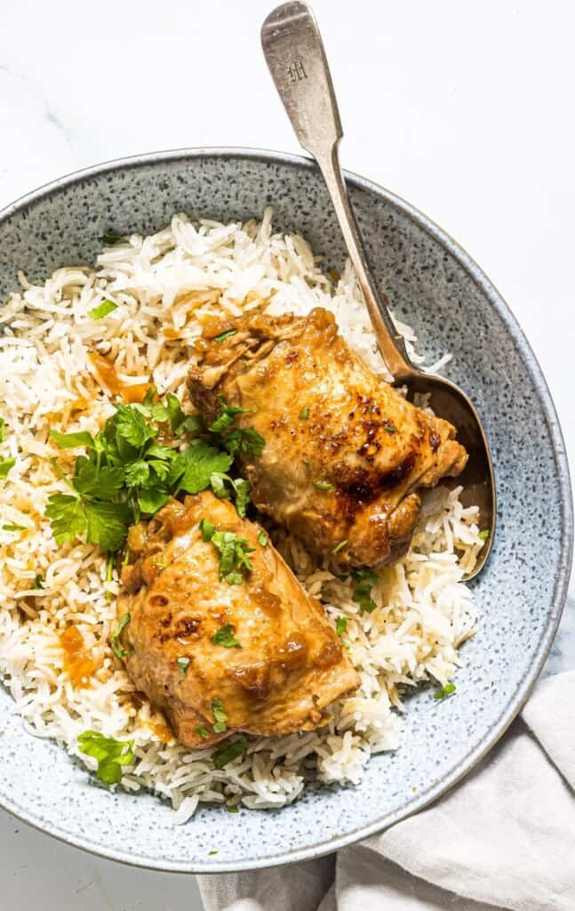 pressure cooker adobong manok on a bed of steamed rice in serving bowl