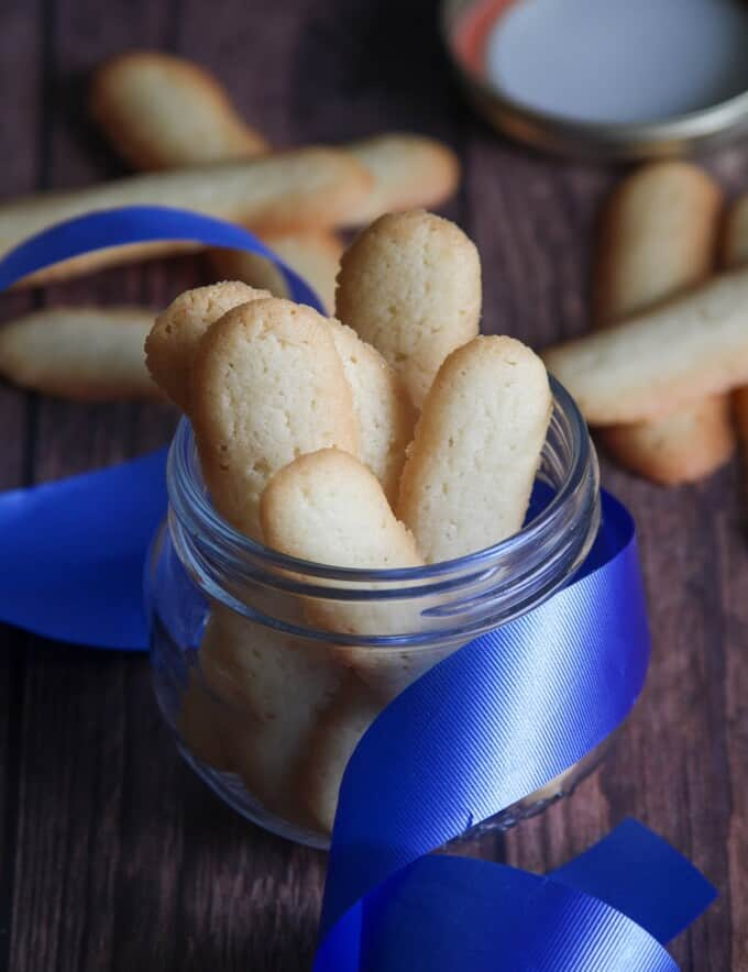 Filipino cat's tongue cookies in a glass jar with blue ribbon