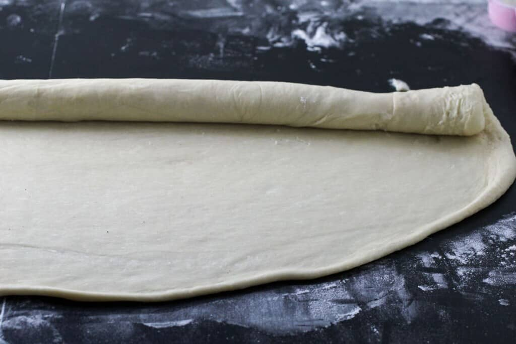 rolling the dough into a cylindrical log