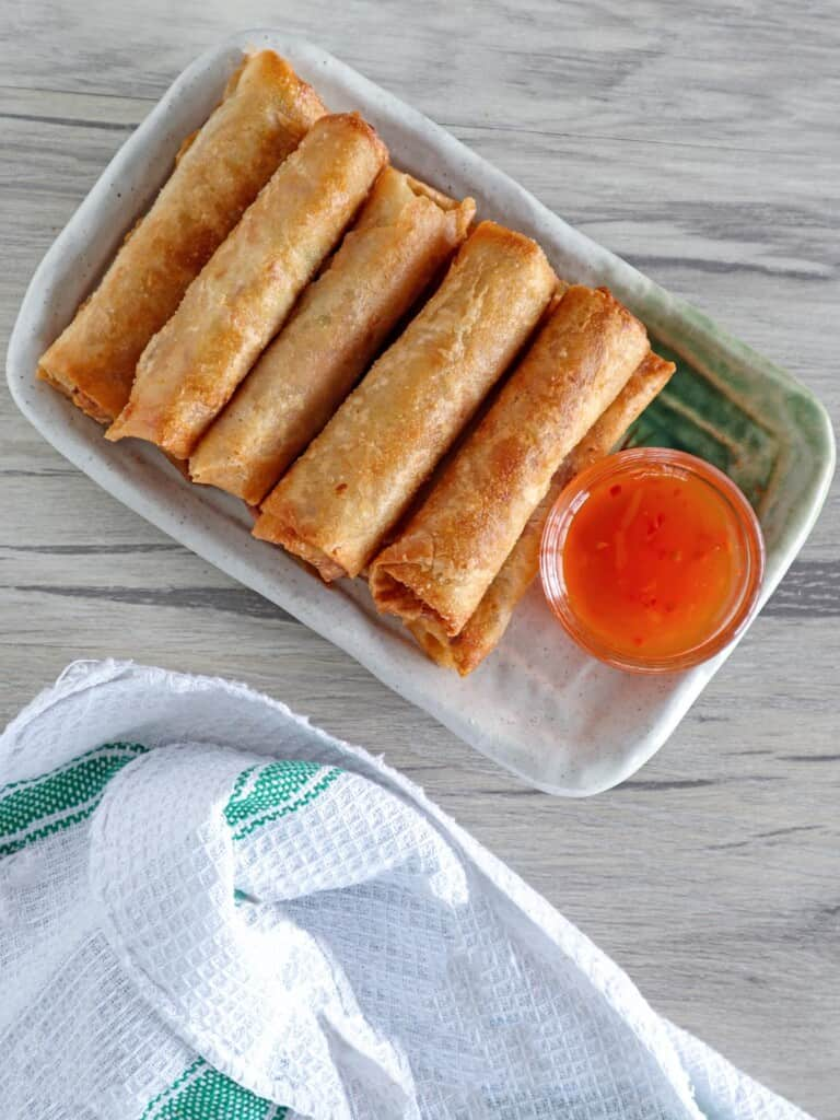tuna spring rolls on a serving platter with a small bowl sweet chili sauce on the side