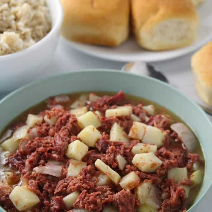 Ginisang Corned Beef in a serving bowl with pandesal and steamed rice on the side