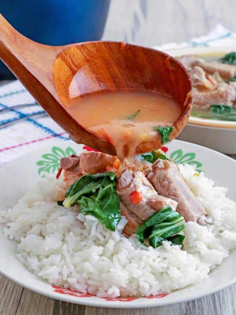 pouring broth over pork kinamatisan on steamed rice on a white plate
