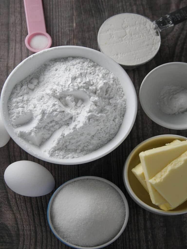 Arrowroot flour, butter, sugar, eggs, baking powder, and flour in individual bowls