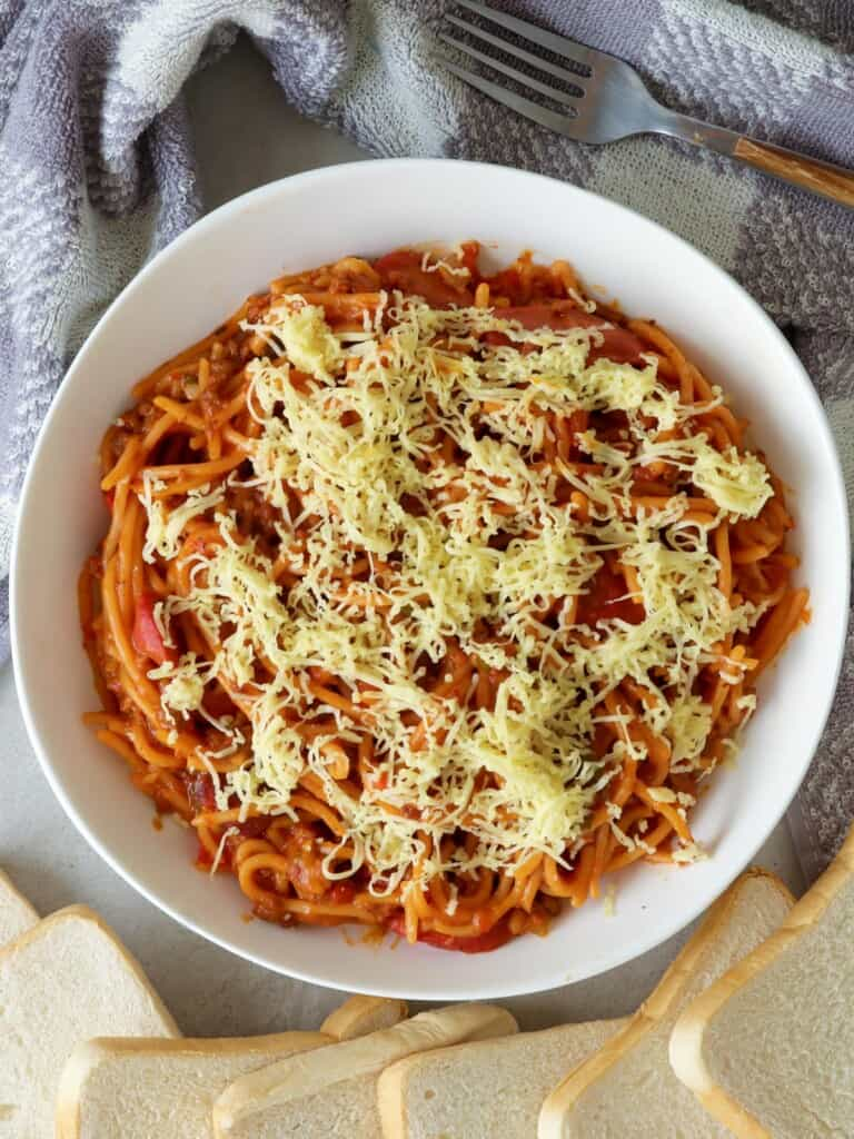 Instant Pot Filipino-style Spaghetti with shredded cheese in a white serving bowl