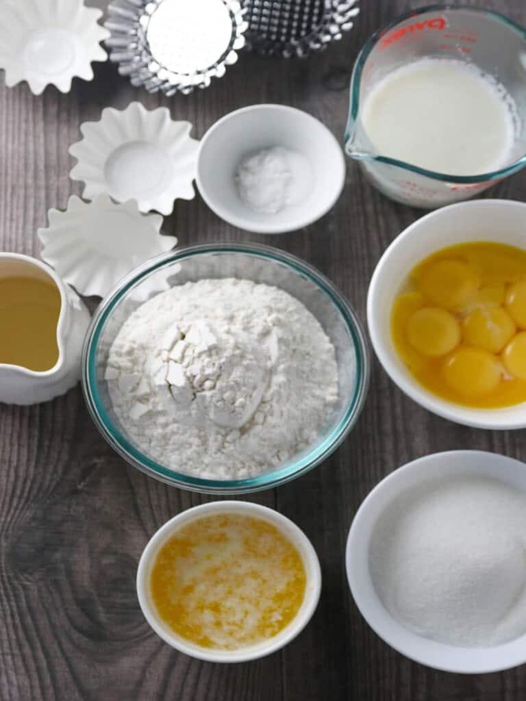 flour, egg yolks, melted butter, sugar, baking powder, muffin tin, milk, oil
