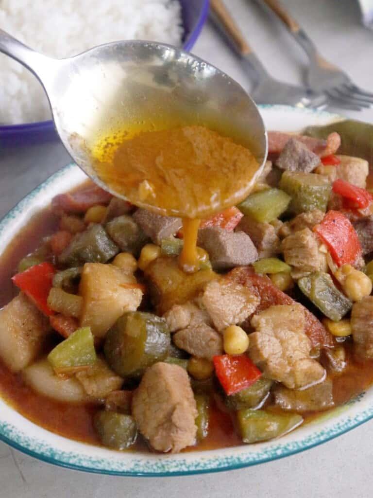 pouring sauce on a platter of Marikina menudo