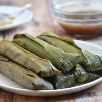 Suman Malagkit wrapped in banana leaves on a serving platter with a bowl of caramel coconut sauce on the side