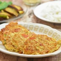 fish omelet with dulong on a serving platter with a plate of steamed rice on the side