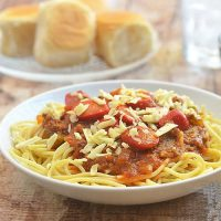 Filipino-Style Spaghetti on a white serving plate with a side of bread rolls