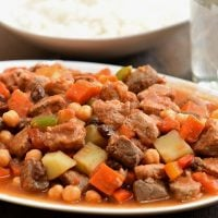Pork Menudo on a serving platter with a side of steamed rice