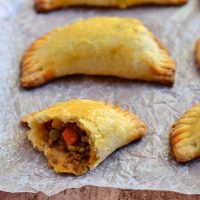empanadas with ground beef filling arranged in a single layer on parchment paper