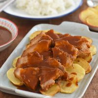 sliced pork asado with tomato sauce and fried potato slices on a serving platter
